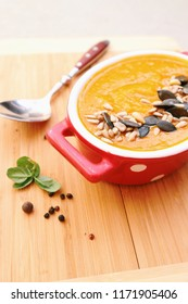 Pumpkin soup in a bowl on a wooden board. Healthy clean eating. Side view.