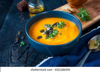 Pumpkin soup in a bowl served with parsley, olive oil and pumpkin seeds. Vegan soup. Dark wooden background.