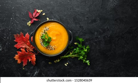 Pumpkin soup with pumpkin and colored autumn leaves. flat lay. On a black stone background. Top view. Free space for your text.