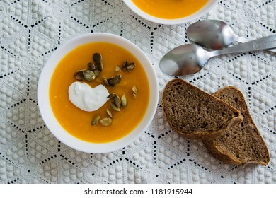 Pumpkin soup with cream, seeds, bread on grunge black background. Top view