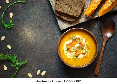 Pumpkin soup with cream, seeds, bread and fresh green in ceramic bowl on grunge black background. Top view.Spaces for text and copy