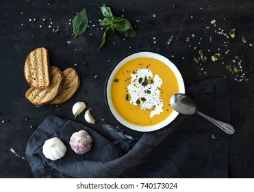Pumpkin soup with cream, seeds, bread and fresh basil in rustic metal plate on grunge black background. Top view