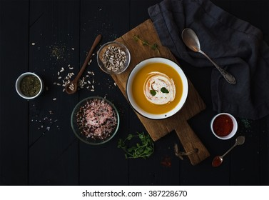 Pumpkin soup with cream, seeds and spices in rustic metal bowl over grunge black background. Top view, horizontal
