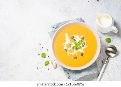 Kürbis-Suppe mit Sahne. Bild mit Draufsicht am weißen Tisch.