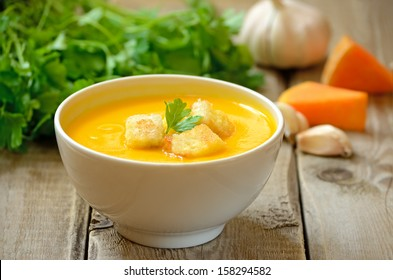 Pumpkin soup with croutons on wooden table
