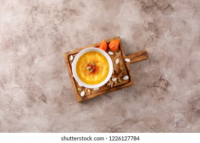 Pumpkin soup on a neutral wooden board decorated with autumn leaves and physalis.