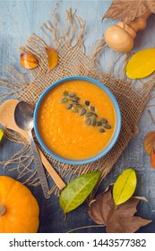 Pumpkin soup on rustic background. Autumn concept with pumpkin and fall leaves. Top view from above