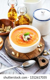 Pumpkin soup on rustic wooden background