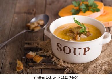 Pumpkin soup  on wooden table. Seasonal autumn food