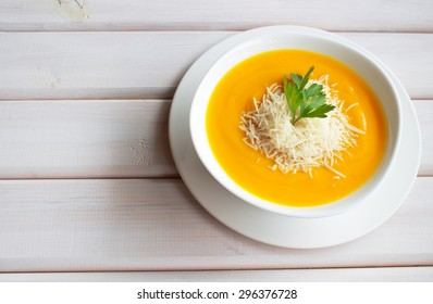 Pumpkin soup on a wooden table with a spoon and bread
