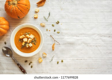 Pumpkin soup and organic pumpkins, top view, copy space. Seasonal autumn food - Spicy pumpkin soup with croutons and pumpkin seeds.