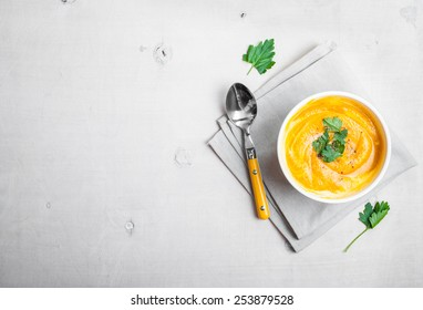 Pumpkin soup with parsley on a white wooden background. Free space for text