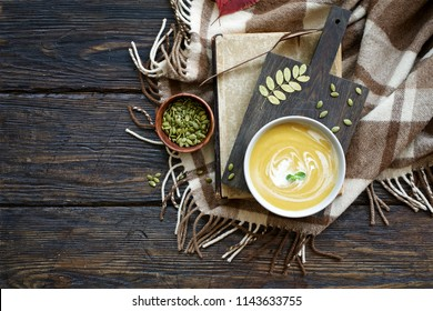Pumpkin soup puree in bowl on dark brown background. Cozy autumn or winter concept