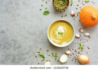 Pumpkin soup puree in bowl on gray background.Top view
