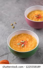 Pumpkin soup puree in ceramic bowls on a gray textured background. Close-up.