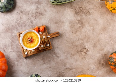 Pumpkin soup puree on a wooden board in a frame of pumpkin vegetables and zucchini. View from above