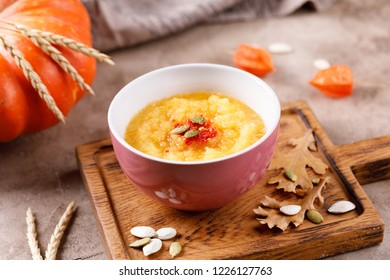 Pumpkin soup puree with pumpkin seeds on a decorative board decorated with autumn leaves.