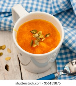 Pumpkin soup with pumpkin seeds in a white circle on the wooden table, selective focus, square