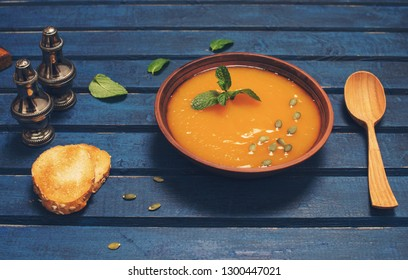 Pumpkin soup selective focus. Seasonal autumn food spicy soup with cream and pumpkin seeds. Roasted pumpkin and carrot soup with cream and pumpkin seeds on blue wooden background