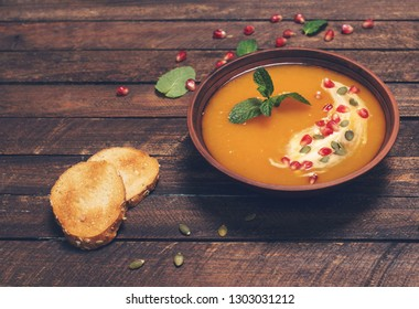 Pumpkin soup selective focus. Seasonal autumn food spicy soup with cream and pumpkin and pomegranate seeds . Roasted pumpkin and carrot soup with cream and pumpkin seeds on wooden background.