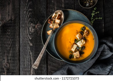 Pumpkin soup served in a bowl with croutons, pumpkin seeds and olive oil. Dark background.