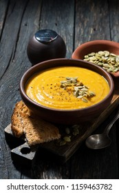 pumpkin soup with toasts on wooden table, vertical