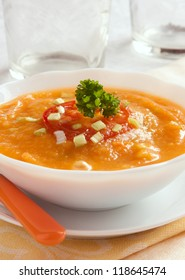 pumpkin soup with tomato and onion in white plate