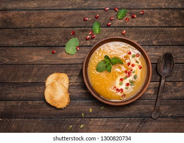Pumpkin soup top view, copy space. Seasonal autumn food spicy soup with cream and pumpkin and pomegranate seeds. Roasted pumpkin and carrot soup with cream and pumpkin seeds on wooden background.