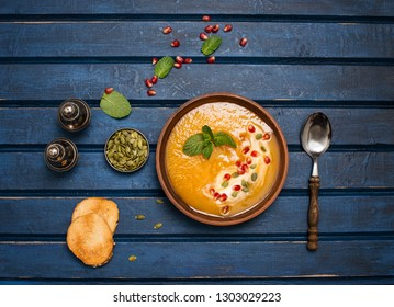 Pumpkin soup top view, copy space. Seasonal autumn food spicy soup with cream and pumpkin and pomegranate seeds . Roasted pumpkin and carrot soup with cream and pumpkin seeds on wooden background.