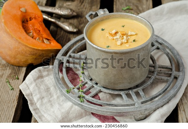 Pumpkin soup in vintage iron cup on iron support with fresh pumpkins and wooden background