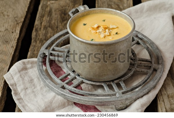 Pumpkin soup in vintage iron cup on iron support and wooden background