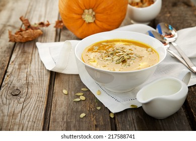 Pumpkin soup in a white cup on wooden background