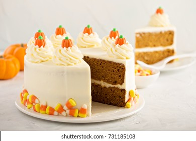 Pumpkin spice or carrot layered cake with cream cheese frosting decorated with candy, dessert for Halloween and Thanksgiving
