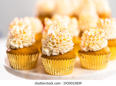 Pumpkin spice cupcake with Italian buttercream and sprinkles on a cake stand.
