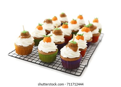 Pumpkin spice cupcakes with vanilla frosting decorated with pumpkins and caramel apples