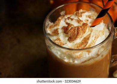 Pumpkin spice latte close up on dark moody background, selective focus