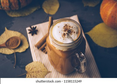Pumpkin spice latte or coffee with cinnamon. Autumn, fall or winter hot drink. Background with yellow leaves
