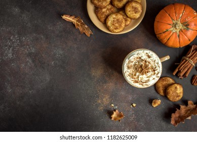 Pumpkin Spice Latte. Cup of Latte with Seasonal Autumn Spices, Cookies and Fall Decor. Traditional Coffee Drink for Autumn Holidays, copy space.