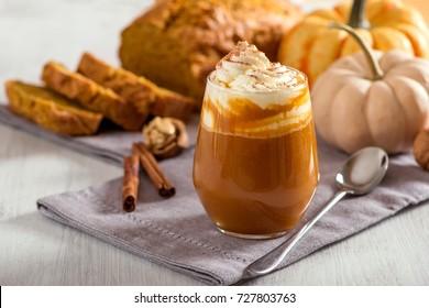 Pumpkin spice latte, hot coffee drink with pumpkins and pumpkin cake bread, healthy autumn dessert food