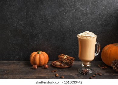 Pumpkin Spice Latte on black wooden background, copy space. Seasonal autumnal coffee drink with spices and organic pumpkins.