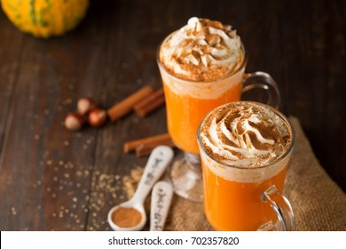 Pumpkin spice latte with whipped cream on top on rustic wooden background. Selective focus. Holiday autumn time concept