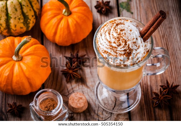 Pumpkin spice latte with whipped cream  on wooden table