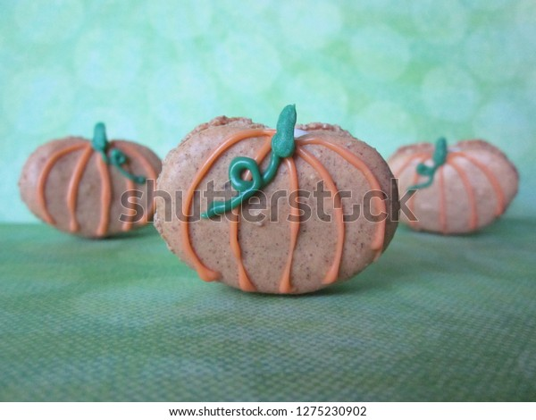 Pumpkin spice macarons decorated with orange and green candy melts