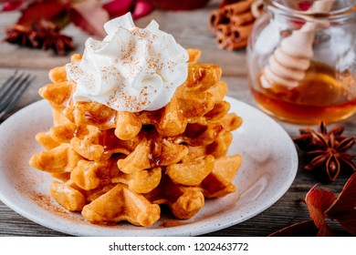 Pumpkin spice waffles with whipped cream on wooden background for Thanksgiving Day.