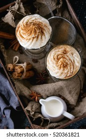 Pumpkin spicy latte  with whipped cream and cinnamon in two glasses standing in wooden box with textile, jug of cream and spices other dark background. Hot sweet coffee drink theme. Top view