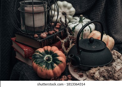 Pumpkin stil life with books, candles, moss and a tea pot. Autumn/Fall, Halloween, Thanksgiving or harvest concept.