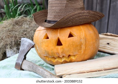 Pumpkin is a symbol of Halloween. Halloween pumpkin head wearing a hat with an ax.
