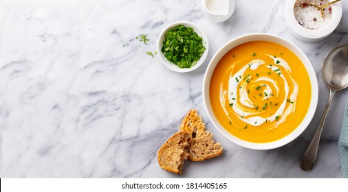 Pumpkin traditional soup with creamy silky texture. Marble background. Copy space. Top view.