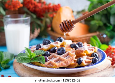 Pumpkin waffles with honey on a blue wooden table