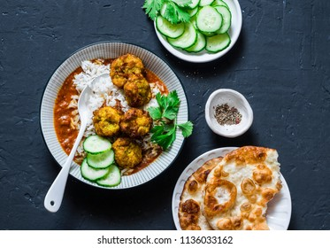 Pumpkin and zucchini fritters meatballs with rice and curry sauce. Healthy vegetarian food on dark background, top view